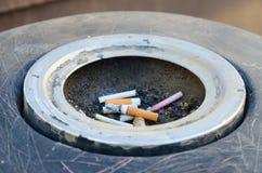 在烟灰缸的烟头在城市街道上 免版税图库摄影