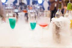 在烟的五颜六色的鸡尾酒在瓶中的酒吧 免版税库存图片