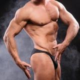 在烟的肌肉爱好健美者 免版税库存照片