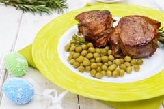 在烟肉、服务用绿豆和迷迭香小树枝包裹的水多的猪肉大奖章在一块板材在白色木背景 库存图片