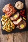 在烟肉包裹的可口切的肉糕用土豆楔住a 免版税库存照片