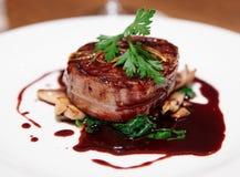 在烟肉包裹的里脊肉牛排用红色调味汁 免版税库存照片