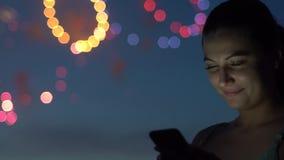 在烟花期间,女孩使用一个智能手机 慢的行动 股票视频