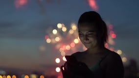 在烟花期间,女孩使用一个智能手机 股票录像