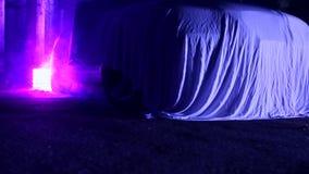 在烟身分的织品盖的汽车在紫色照亮的被放弃的房子 股票录像