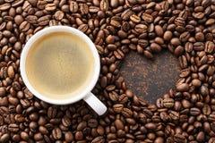 在烤咖啡豆和心形的框架的咖啡杯 免版税库存照片