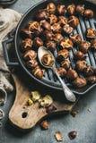 在烤在木板的生铁的烤栗子平底锅 免版税库存图片