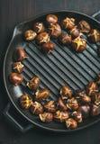 在烤平底锅的烤栗子在黑暗烧焦了木背景 免版税库存图片