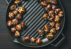 在烤平底锅的烤栗子在黑暗烧焦了木背景 免版税库存照片