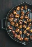 在烤平底锅的烤栗子在黑暗的木背景 库存图片