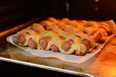在烤箱烘烤的香肠面团 免版税库存图片