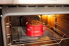 在烤箱烹调的一个红色杯子的一大豪华的红润mugcake 烹调和杯形蛋糕食谱现实主义 免版税库存图片