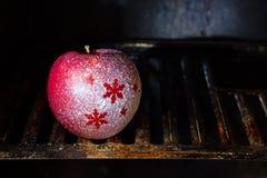 在烤箱的圣诞节多雪的抽象苹果在烘烤的概念前 免版税库存照片