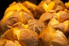 在烤箱的撕开的被烘烤的patatoes 图库摄影