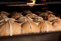 在烤箱的烘烤的新鲜的自创有十字架形的圆形圣糕 免版税库存图片