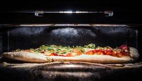 在烤箱的自创薄饼 免版税图库摄影
