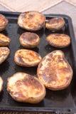 在烤箱的被烘烤的土豆在煎锅 免版税图库摄影