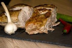 在烤箱红辣椒木背景大蒜黑背景中烘烤的肉 图库摄影