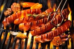 在烤肉格栅的香肠与火焰 免版税库存照片