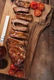 在烤肉汁和蜂蜜的猪排烤了在一个木板的蕃茄 对啤酒的一顿伟大的快餐在一张土气木桌上 顶视图 库存照片