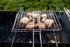 在烤肉被烤的一些肉串特写镜头  烤在格栅的用卤汁泡的shashlik 免版税图库摄影