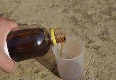 在烧杯的倾吐的厚实的草甘膦解答 免版税图库摄影