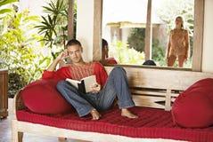 在热带假期的夫妇,读。 免版税库存图片