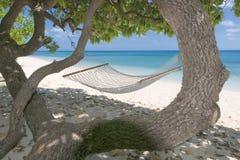 在热带天堂绿松石水沙子海滩的一个吊床 免版税库存图片