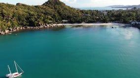 在热带岸附近的小船 现代游艇航行令人惊讶的寄生虫视图在风平浪静水的在海岸热带火山附近 股票视频