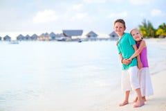 在热带手段海滩的二个孩子 免版税库存图片