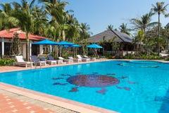 在热带手段的游泳池与棕榈树 库存照片