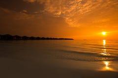 在热带手段的美好的日落与overwater平房 免版税库存照片