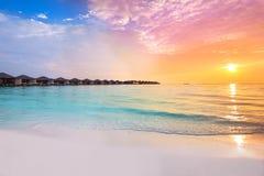 在热带手段的美好的日落与overwater平房 免版税库存图片