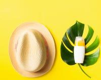 在热带植物夏天帽子明亮的黄色背景大板料的遮光剂  夏天休假概念和海滩 库存照片