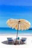 在热带沙子的海滩睡椅和伞靠岸 免版税库存照片