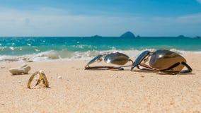 在热带海岛、两个婚戒和太阳镜上的蜜月 库存照片