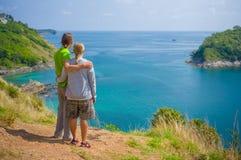 在热带海岛峭壁的男人和妇女容忍 图库摄影
