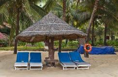 在热带海岸的Deckchairs热带沙子海滩棕榈树 免版税库存图片