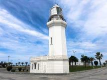 在热带海温暖的避暑胜地的大高石白色灯塔有反对天空蔚蓝的棕榈树的 免版税图库摄影