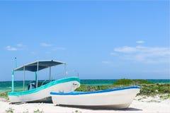 在热带海滩一起栓的两个小渔船 免版税库存图片