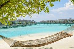 在热带海滩的吊床与在手段的结束水别墅 库存照片