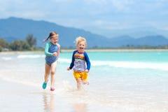 在热带海滩的孩子 儿童使用海上 免版税库存照片
