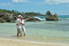 在热带海滩的年长夫妇休息 免版税库存图片