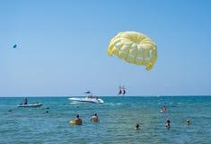 在热带海滩的愉快的夫妇帆伞运动在夏天 在垂悬空中的降伞下的夫妇 儿童有父亲的乐趣一起使用 热带的天堂 假定 免版税库存图片