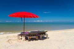 在热带海滩的红色遮阳伞 库存照片