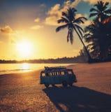 在热带海滩的葡萄酒微型搬运车在日出 免版税库存图片