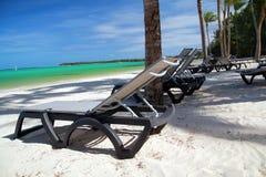 在热带海滩的躺椅 免版税库存图片