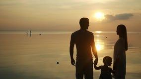 在热带海滩看看的父亲、母亲和女儿立场日落 爸爸和妈咪保留女儿的手 慢的行动 股票视频