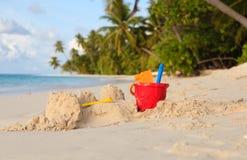 在热带海滩和玩具的沙子城堡 免版税图库摄影