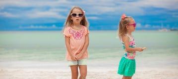 在热带海滩期间的两个小女孩 库存照片